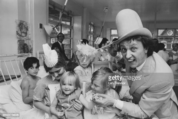 English comedian singer and entertainer Ken Dodd pictured with nurses and patients on a ward during a visit to Great Ormond Street Hospital in London...