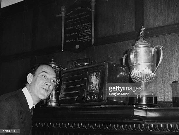 English comedian Tommy Trinder Chairman of Fulham Football Club listening to the fixtures being drawn for the FA Cup in his office at Craven Cottage...