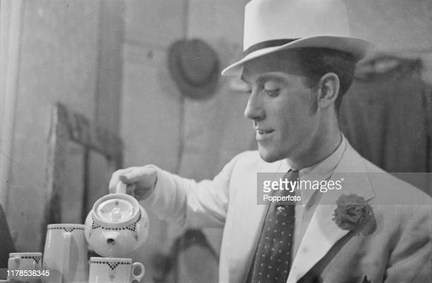 English comedian Tommy Trinder pours tea from a teapot in to a cup in his dressing room backstage prior to a performance in Blackpool England during...