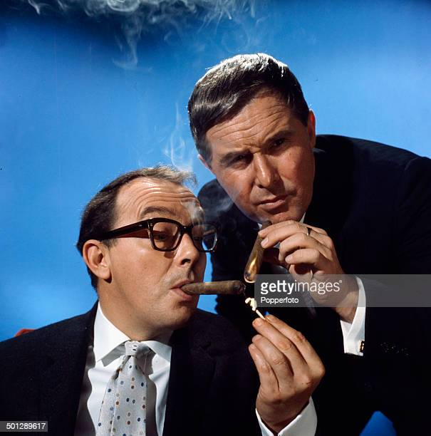 English comedians Eric Morecambe on left and Ernie Wise of the comedy duo Morecambe and Wise posed together with cigars in 1966