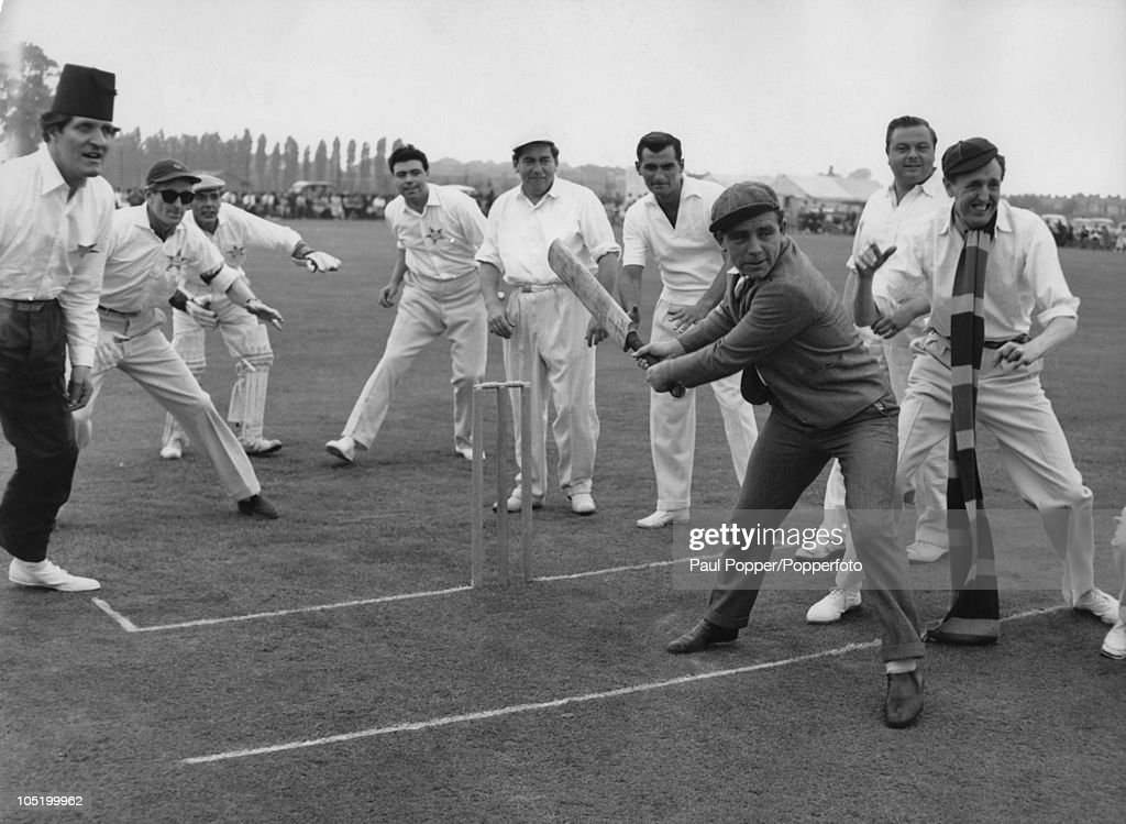 English comedians Tommy Cooper (1921 - 1984, left) and Norman Wisdom (1915 - 2010) playing a charity cricket match at Sudbury, Middlesex, in aid of victims of cerebral palsy, 23rd July 1956.