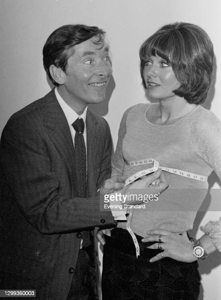 English comedy actor Kenneth Williams measures the bust of co-star Jennie Linden, UK, 1st November 1972. They are starring together in 'My Fat...