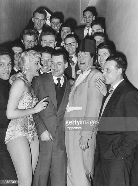 English comedy conjuror Tommy Cooper and showgirl Ilona Adams backstage with members of the Peterborough United football team at a Folies Bergere...