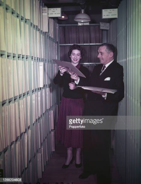 English comic actor and comedian Jack Train and BBC producer Monica Chapman select discs in the BBC record library in London in November 1955 Monica...