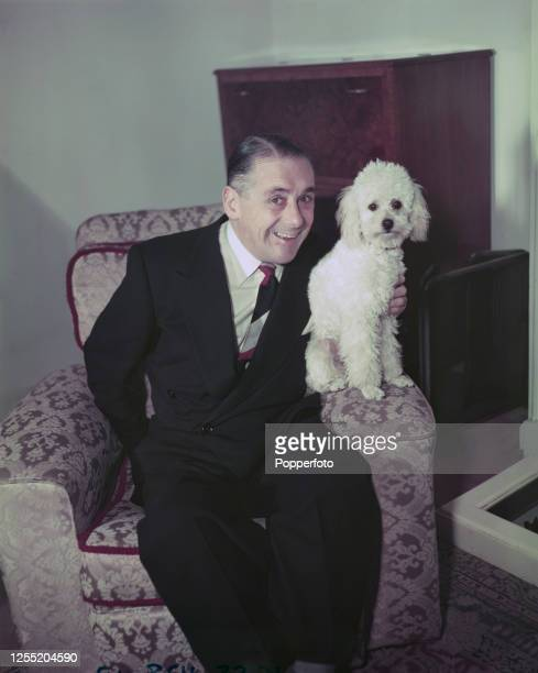 English comic actor and comedian Jack Train posed with his dog Buttons in his living room at home in December 1955