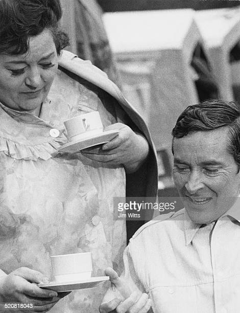 English comic actor and comedian Kenneth Williams takes a cup of tea from his costar English comedy actress Hattie Jacques during a break from...