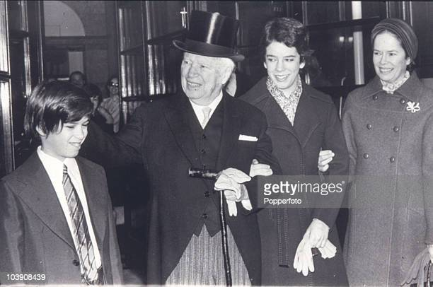 English comic actor Charlie Chaplin at Buckingham Palace to receive his knighthood London 4th March 1975 With him are his wife Oona O'Neill son...