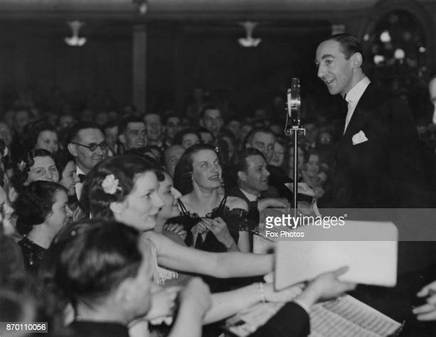 English comic actor Claude Hulbert is approached by autograph hunters during a gala dance to celebrate the reopening of the Regent Dance Hall in...