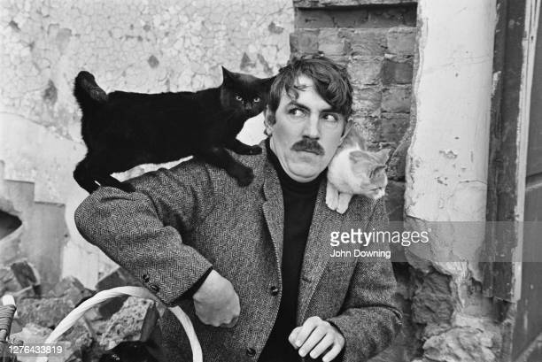 English comic actor Peter Cook with his cats, November 1965.