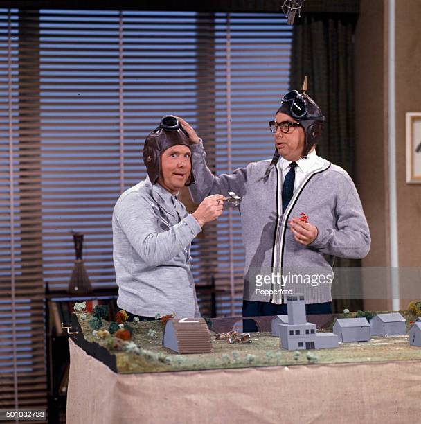 English comic due Eric Morecambe on right and Ernie Wise of Morecambe and Wise perform together with aviator helmets and goggles and model aeroplanes...