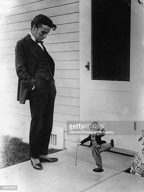 English comic film actor and director Charles Chaplin looks down at a kneehigh model doll of himself wearing his familiar costume of bowler hat baggy...
