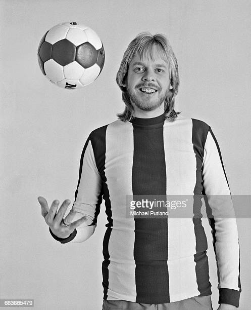 English composer and keyboard player Rick Wakeman tossing a football March 1983