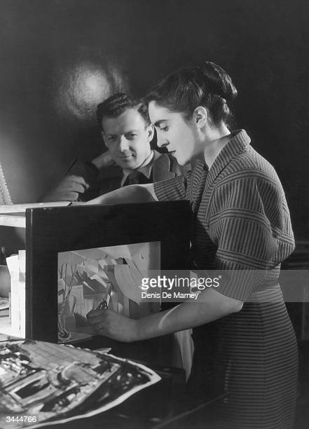 English composer Benjamin Britten watches set designer Tanya Moiseiwitsch at work on a miniature stage possibly for a production of Britten's...