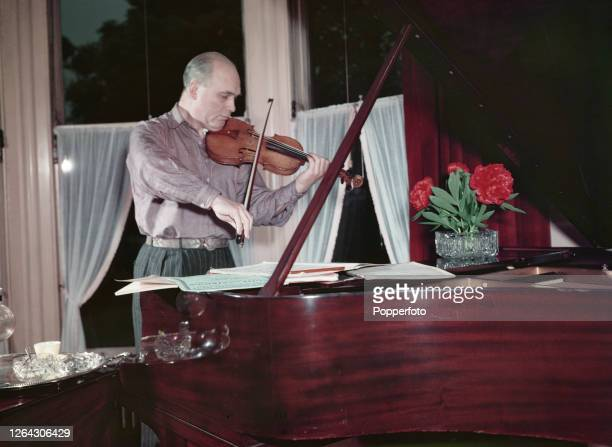 English conductor and violinist Hugo Rignold plays a violin at home in England in June 1952