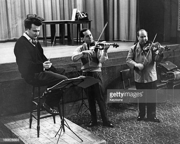 English conductor Colin Davis rehearsing with Soviet violinists David Oistrakh and his son Igor Oistrakh at St Pancras Town Hall London 17th February...
