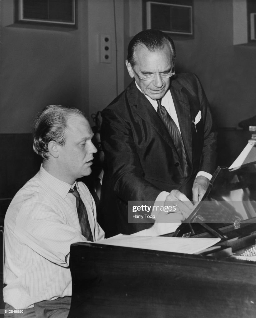 English conductor Sir Malcolm Sargent (1895 - 1967, right) talks to pianist Robin Harrison (1932 - 2013) before a rehearsal of Stravinsky's 'Petrouchka' at the Maida Vale Studio, London, 24th July 1964. They are getting ready for the Promenade concert at the Royal Albert Hall.