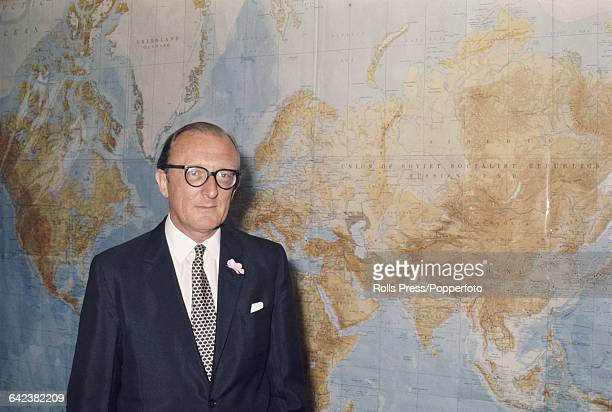 English Conservative Party politician and newly appointed Secretary of State for Defence Peter Carington pictured standing in front of a large map of...