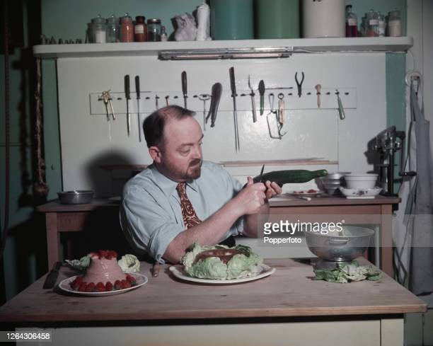 English cook and television chef Philip Harben prepares dishes including a strawberry mousse in his kitchen at home in London in July 1952