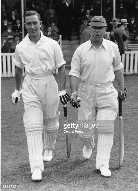 English cricketer and footballer Denis Compton of Middlesex County Cricket Club walks out with team mate Elias 'Patsy' Hendren before a match against...