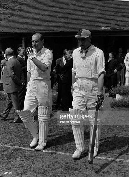 English cricketer Douglas Jardine walks out to bat in a charity match.