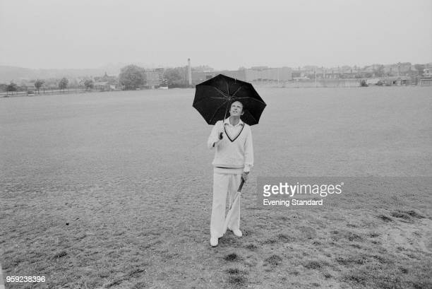 English cricketer Geoffrey Boycott standing with an umbrella on a cricket pitch, UK, 29th June 1978.