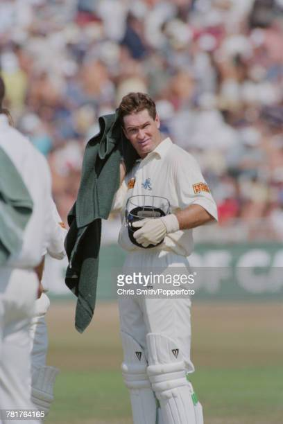 English cricketer Graeme Hick of the England cricket team wipes his head with a towel as he bats for England against West Indies during the 5th Test...