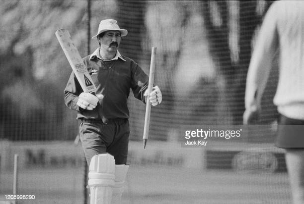 English cricketer Graham Gooch carrying a stump and a cricket bat, and wearing a bucket hat during a practice session in the nets in Essex, England,...