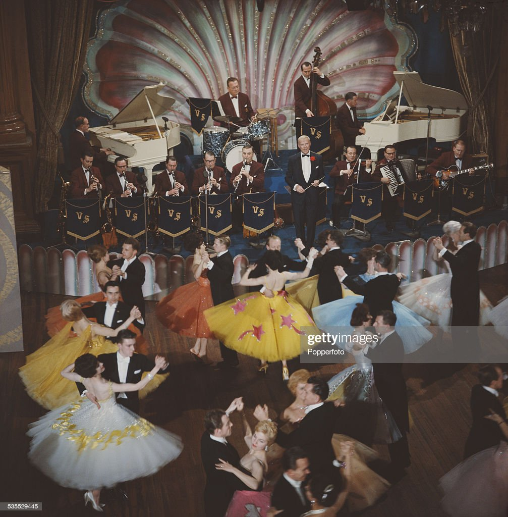 English dancer and bandleader, Victor Silvester (1900-1978) leads his big band on stage in front of ballroom dancers during filming of the television series 'Dancing Club' in 1962.