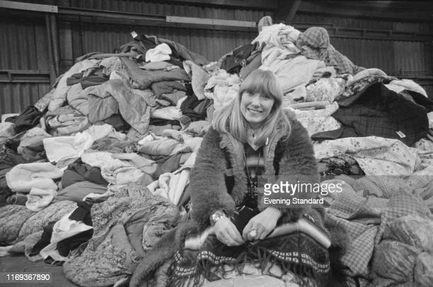 English dancer and television presenter Lesley Judd sitting near a pile of clothes UK 7th December 1976