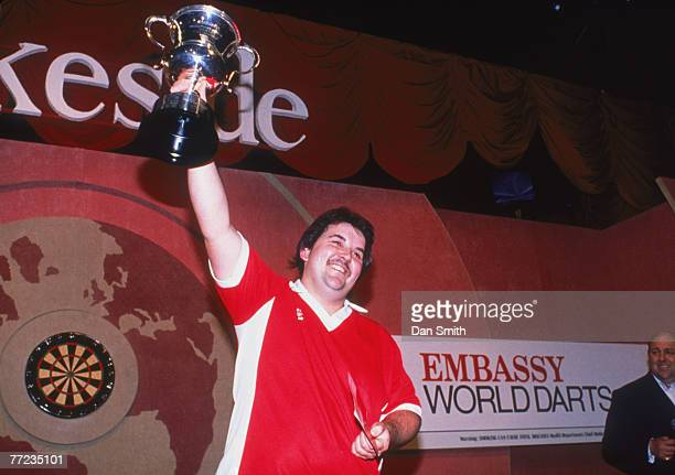 English darts player Phil Taylor lifts the trophy after winning the World Professional Darts Championship at the Lakeside Country Club at Frimley...