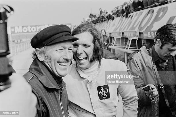 English design engineer, inventor, and founder of Lotus Cars, Colin Chapman with Brazilian racing driver Emerson Fittipaldi during practice runs at...