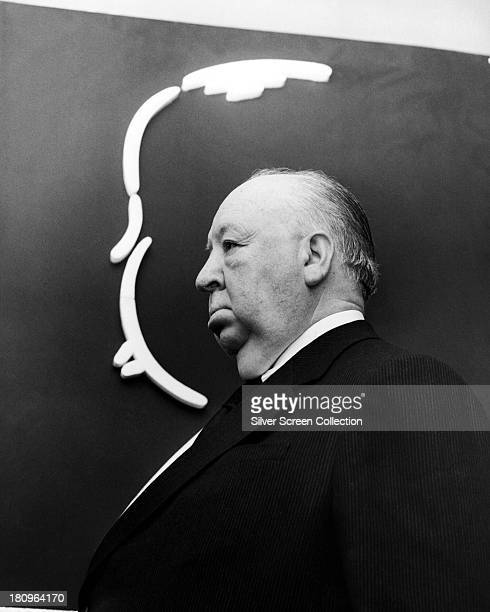 English director Alfred Hitchcock posing next to a drawing of his profile in a promotional portrait for the TV anthology series 'Alfred Hitchcock...
