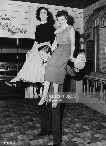 English disc jockey and manager of the Plaza Ballroom in Manchester Jimmy Savile lifting two young women and a barbell April 1956