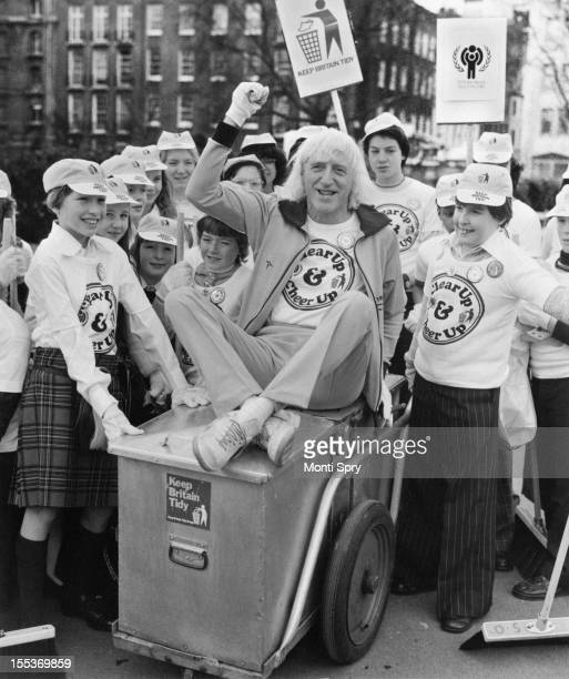 English disc jockey and television presenter Jimmy Savile in Victoria Embankment Gardens London with the children who invented the slogan 'Clear Up...