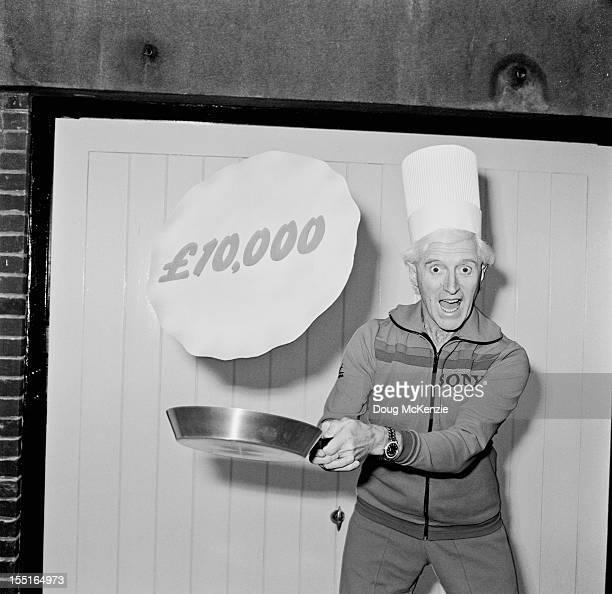 English disc jockey and television presenter Jimmy Savile pretends to toss a 10000 pound pancake February 1980