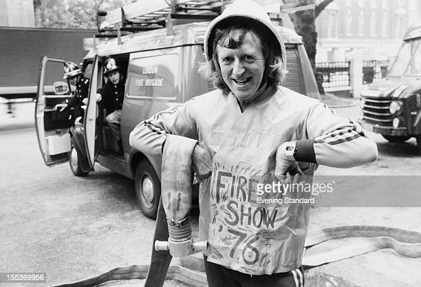 English disc jockey and television presenter Jimmy Savile with members of the London Fire Brigade at Fire Show 76 May 1976