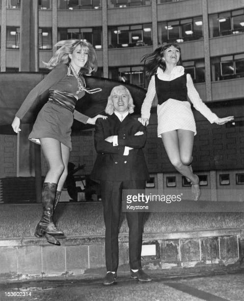 English disc jockey and TV presenter Jimmy Savile at BBC TV Centre with Nova SainteClaire and Chris Marlowe who have been chosen to be the hostesses...