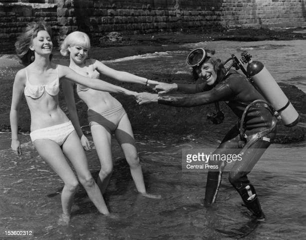 English disc jockey and TV presenter Jimmy Savile with his secretaries Barbara Counsel and Christine McCarthy on the beach at Scarborough Yorkshire...