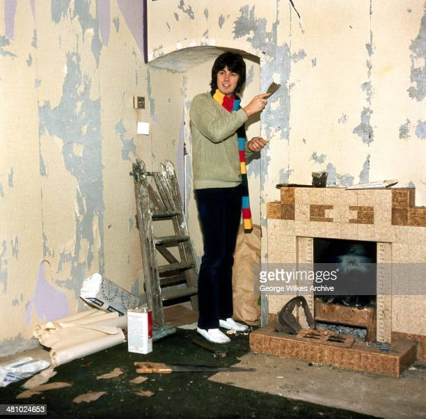 English disc jockey journalist and television personality Mike Read scrapes paint off a wall above a fireplace London England 1981