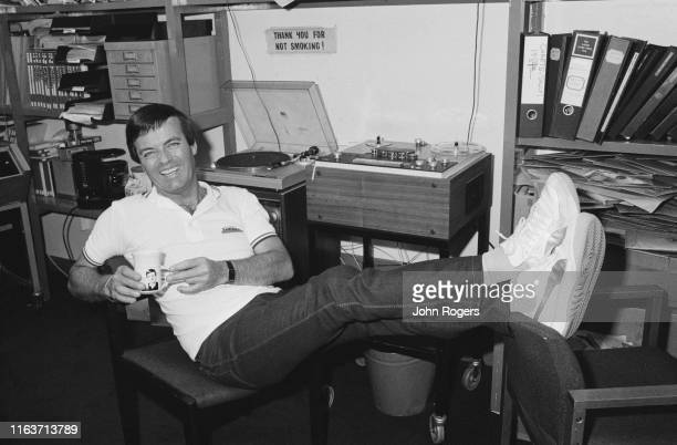 English disc jockey Tony Blackburn lounges on a chair while holding a mug with his face printed on it, UK, 8th August 1984.