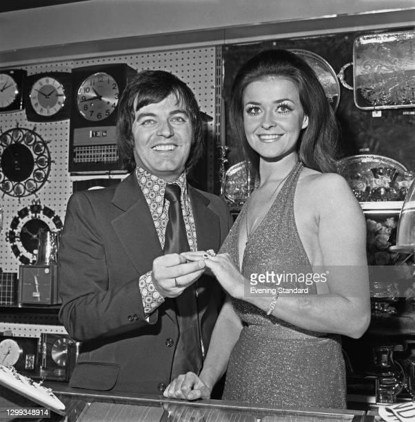 English disc jockey Tony Blackburn pretends to propose to Jenny McAdam, Miss United Kingdom, UK, 13th November 1972.