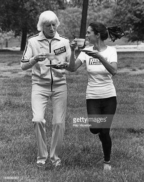 English dj and television presenter Jimmy Savile and model Sharon Moss drinking tea while jogging in Hyde Park London 6th June 1979 They are...