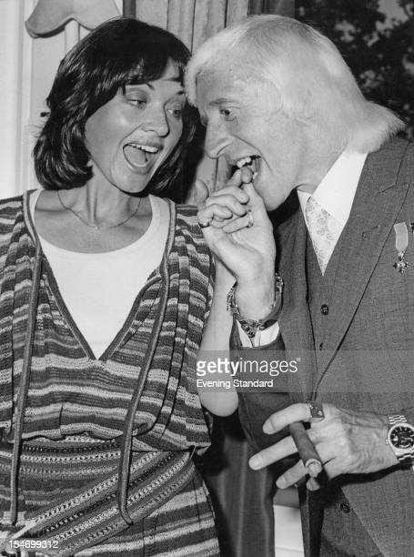 English dj and television presenter Jimmy Savile bites the finger of British ITN newsreader Anna Ford at a Dorchester Hotel luncheon London 19th June...