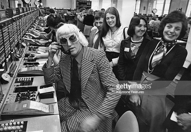 English dj and television presenter Jimmy Savile making a call from the Wren House International Telephone Exchange in London 14th April 1975 Savile...