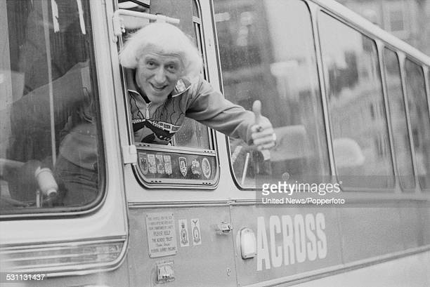English DJ and television presenter Jimmy Savile pictured in the driver's seat of a Jumbulance coach in London on 14th January 1977