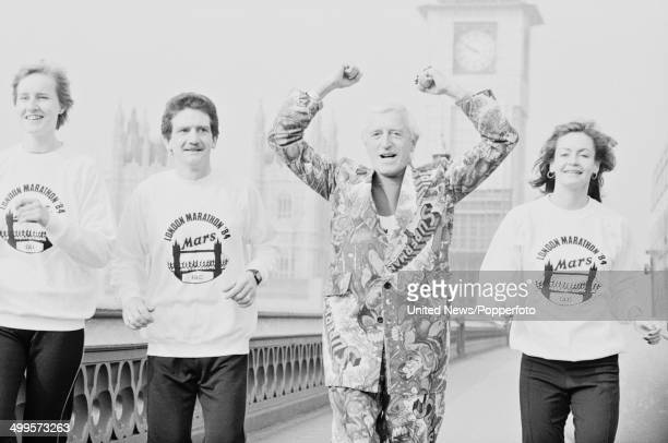English DJ and television presenter Jimmy Savile pictured running over Westminster Bridge to publicise the upcoming marathon in London on 14th March...