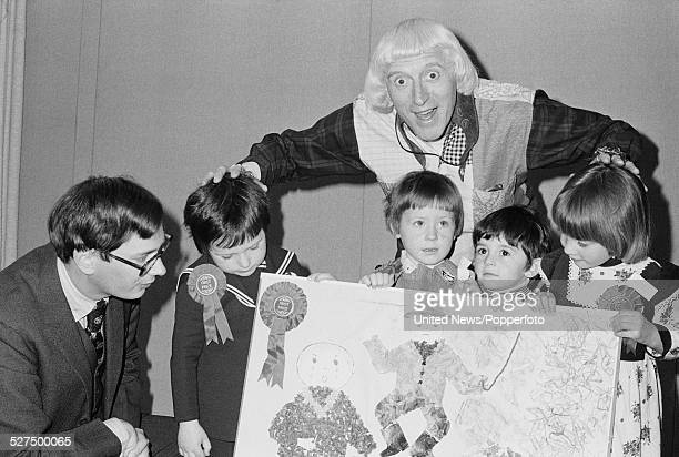 English DJ and television presenter Jimmy Savile pictured with young children and artwork at the Child Farm Safety Awards in London on 3rd May 1977