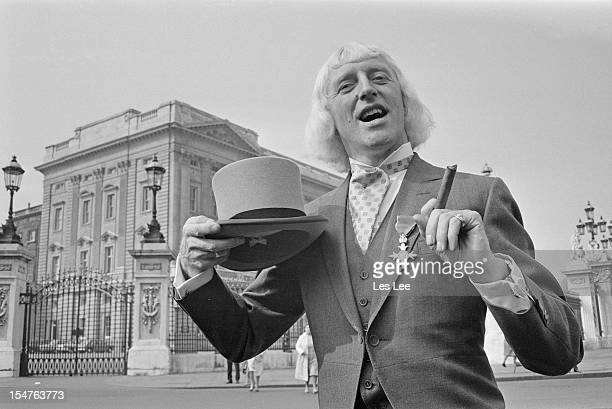 English dj and television presenter Jimmy Savile showing off his OBE after his investiture at Buckingham Palace London 21st March 1972