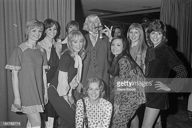 English dj and television presenter Jimmy Savile shows off his OBE to members of the 'Second Generation' song and dance troupe March 1972