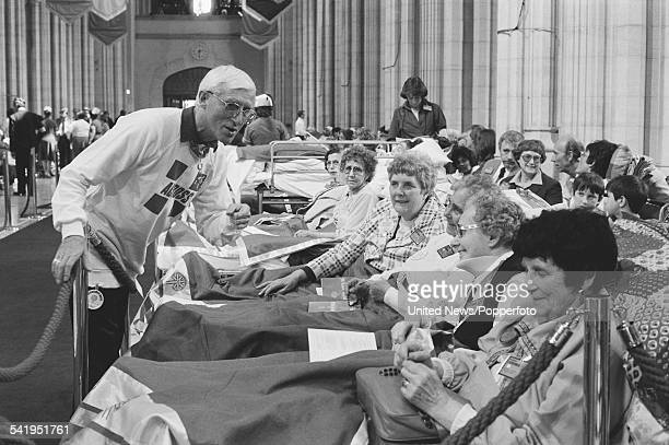 English DJ and television presenter Jimmy Savile talks with hospital patients prior to a visit by Pope John Paul II to St George's Cathedral...